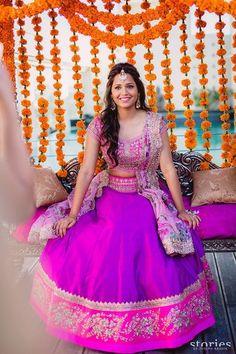 purple lehenga , purple blouse , floral print dupatta , mehendi hairstyle , stage backdrop , short sleeves blouse , pink and purple lehenga