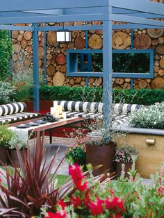 Sculptural and Functional Cut logs create a whimsical wall between areas in this backyard living space. The stick-straight blue pergola, trim and window contrast the wall's organic shapes and give the room a sculptural feel.