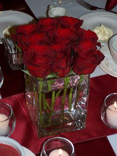 Red Rose Square Vase Centerpiece with small votives with little white flickering candles.  Plus a shiny red table cloth.  That looks cheap, easy and pretty.