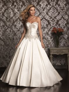 Style: 9003  An exquisite ball gown in rich satin. The strapless bodice features a sweetheart neckline and flattering ruching while Swarovski crystals encrust the entire bodice.  Colors: White/Silver, Ivory/Silver  Fabric: Satin-Back Taffeta  Sizes: 2 - 32