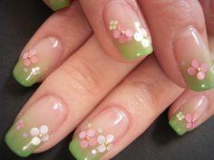 Bella nail art con smalto verde sfumato fino alla trasparenza, fiori creati applicando perline dorate e dischetti colorati.