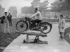 """A 14-year-old strongman calling himself """"Boy Samson"""" supports a 200-pound motorcycle and its rider, 1932"""