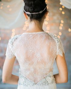 the prettiest lace detailing | photo @tracyenoch event coordination @urbanmagevents florist @lizziebeesweddings venue @lot207 wedding dress @neimanmarcus hair  makeup @eblairmakeuphair wedding cake @thebutterflycakefactory rentals @classicparty chairs and rug @juniperrentals wedding invitations and paper goods @5by7designs #onRuffled #weddingdress #lacedress #headbands #romanticweddings by ruffledblog