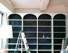 DIY Arched Bookshelves using $50 IKEA bookcases and MDF board. Love the dark background, especially if you cannot paint rental walls.