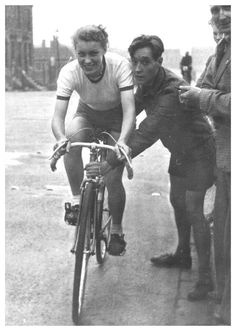 A very young Beryl Burton (17 years old) gets ready to be pushed off in her first race, a 10-mile time trial, at the start of her bike racing career