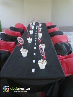 Mesa ambientada con pista central y centros de mesa de golosinas con personajes de la película.