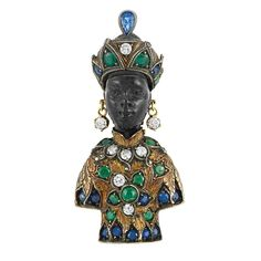 Gold, Silver, Sapphire, Emerald & Diamond Blackamoor Clip, G. Nardi - 18 kt., the carved ebony blackamoor wearing a turban topped by one pear-shaped sapphire & one oval faceted domed garnet, accented by one round diamond & 6 round sapphires & emeralds, with dangling diamond earrings, adorned with an engraved tunic embellished by 5 round diamonds, 16 round sapphires & emeralds & one round cabochon emerald, signed G. Nardi, approximately 15.6 dwt.