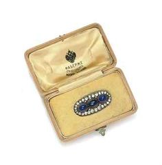 A JEWELLED PLATINUM AND GOLD BROOCH  BY FABERGÉ, ST PETERSBURG, 1908-1917  Lobed oval, centring three cabochon sapphires within a diamond-set border, with a silk and velvet-lined wood box stamped in Russian 'Fabergé St Petersburg Moscow, London' beneath the Imperial warrant, marked on pin.