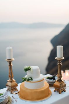 Gold wedding cake, flowers lily of the valley, chandelier, on th edge, caldera view,  santorini