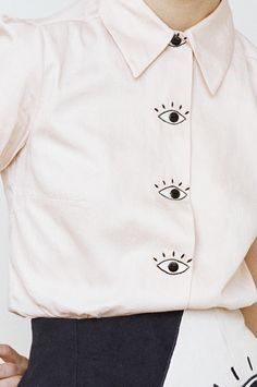 Cotton blouse with hand-embroidered eyes and black buttons. Please don't hesitate to reach out with any size questions. MORE IN PINK COMING SOON