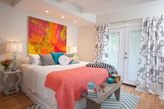 The+white-walled+master+bedroom+pops+with+color+and+bold+patterns.+A+bright+painting+hangs+above+the+bed+and+is+complemented+by+a+coral+quilt+and+colorful+toss+pillows.++