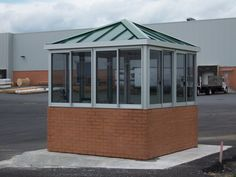 Duraluminum guard booths can be enhanced with a variety of architectural features. This unit includes a factory applied brick that matches the brick exterior of the main building. As standing seam roof was added to complete the look. Standing Seam Roof, Farm Gate, Architectural Features, Site Design, Gazebo, Brick, The Unit, Outdoor Structures, Exterior