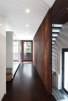 A grille of walnut slats, designed by Syme and made by the local millworkers MCM, delineates the edge of a new stair with open treads made of hot-rolled steel. Tall Bulthaup cabinets mark the edge of the dining area; Evans, a mechanical engineer, had them custom-made to conceal heating ducts that vent almost invisibly through the top edge. Courtesy of: Nathan Dykstra