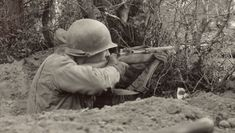 In another dramatic photograph brought back to life, a US soldier is seen keeping aim with his rifle while inside a trench. During the Second World War, the United States was the only country to give its soldiers an auto-loading rifle Military Photos, Military History, Ww2 History, Military Humor, Military Veterans, George Patton, M1 Garand, Colorized Photos, Ww2 Photos