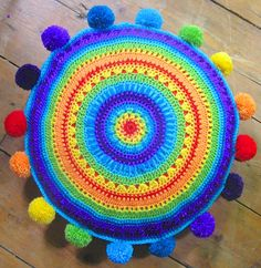 Rainbow  mandala cushion with rainbow pom poms.