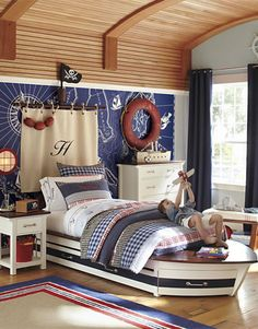 The excitement of pirate ships and high-sea adventures inspired this room. The centerpiece of the room is a boat-shaped bed with a canvas sail in place of a headboard and a porthole-style sconce in place of a bedside lamp. A curved plank ceiling has the feel of an inverted boat hull, and a vintage red life ring and fenders add color and authenticity to the theme.
