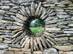Window in a rock wall.  Can be DIY in a loose-laid wall, but it's tricky. Use a round template and a bit of mortar of adhesive until the window is built.