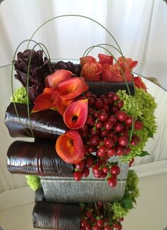 Mango callas, red hypericum berries, roses and folded red leaves with touches green to brighten it make this a abundant floral arrangement  -  hidden garden floral studio, los angeles