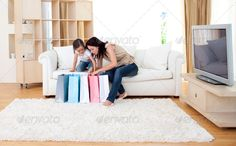Jolly mother and her daughter at home after shopping ...  adult, attractive, bag, beautiful, beauty, blue, buy, caucasian, cheerful, child, clothes, cute, daughter, dress, fashion, female, fun, gift, girl, happy, home, joy, kid, lady, lifestyle, living, looking, mom, mother, people, person, pretty, retail, room, sale, shop, shopper, shopping, smile, sofa, together, trying, woman, women, young
