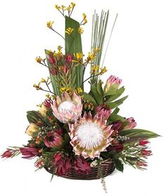 A traditional style long lasting Australian native flower arrangement, typically including king proteas native to South Africa, banksia, gum, liatris, spear grass and red and green foliage.