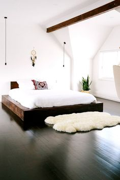 Bright boho bedroom with dark wood floors, a wood floating bed frame, and a lamb throw