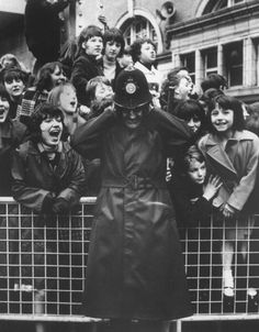 """thegilly: """" A policeman holding his ears in anguish as a pack of teenage girls scream behind a barricade for the, The Beatles, 1966. Photo by Time Life Pictures """""""