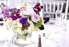 Low centerpiece with Ivory and purple floral. www.tsweddings.com
