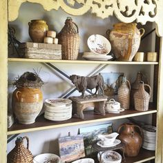 Shelves styled with French antiques, wicker-wrapped bottles & art - Chateau Sonoma