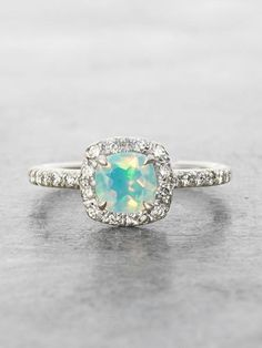 Flashing with Opalescent Rainbows, an ethereal 8mm? cushion cut Ethiopian Opal is surrounded by a halo of Brilliant cut white VS Diamonds in this heavenly ring. Solid 14K White Gold. Handcrafted with
