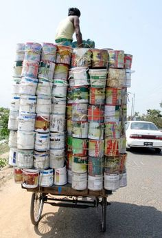 This is the way freight is transported in India - a bicycle rickshaw loaded with paint cans and topped with a laborer.