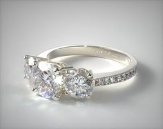 This 14k white gold three stone round and pave set diamond engagement ring is…