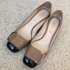 """Two-tone Prada Patent Block Heel Pumps Reposhing - Lovely two-tone black & tan patent pumps with silver buckle detail (embossed w/ Prada). I would keep these except that they're a little too large for me even with inserts (I typically wear US 9 or 39.5 in Prada/Miu Miu). There are some scuffs on the exterior. The top front of the right shoe has a wrinkle in it, but these are otherwise in great condition. The heel is approx. 2 1/4"""" high. There is some wiggle room in the price to allow for a…"""
