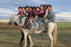 Overloaded pony in Mongolia carrying 9 children