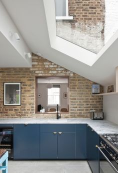 See How Archer + Braun Gave This London Row House a Modern Makeover kitchen with exposed brick wall and blue cabinets Architectural Digest, Patio Interior, Interior Design, Kitchen Diner Extension, Kitchen Extension Pitched Roof, House Extension Design, Row House Design, Exposed Brick Walls, Exposed Brick Kitchen