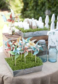 metal buckets with flowery moss: pinwheel favors for kids and bags of chocolate covered sunflower seeds to eat + flower seeds to plant