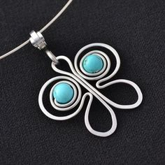 Butterfly pendant on a string. Made of wrought stainless steel wire and turquoise beads.
