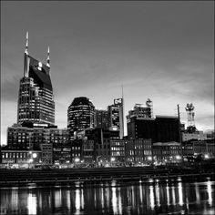 "Downtown Nashville Skyline along the Cumberland River at Dusk. As 22"" x 22"" Matte Black Metal Framed Print."