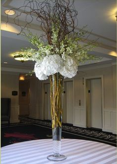 tall cylinder vases with bells of Ireland, white dendrobium orchids, and white hydrangeas with a little bit of brown curly willow.