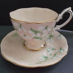 A circa 1940's Royal Albert, bone china, cup and saucer set in the Laurentian Snowdrop pattern. A beautiful vintage footed cup and saucer with a pale