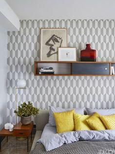 Papel pintado en blanco y gris de Cole & Son, y la pintura Parma Gray de la línea Farrow & Ball, decoran las paredes de este dormitorio de invitados. En la mesilla un lámpara moderna de Michael Anastassiades para Flos. La cama es de Flexform y tiene una funda de Osborne & Little. El gran dibujo en la parte superior de la pared es de 1950, de Joe Bradley.