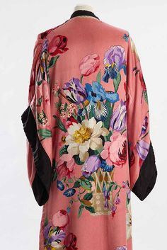 1920s dressing gown | 1920s silk satin printed dressing gown with very large naruralistic irises, roses, tulips and other flowers on a pink ground. The Kimono typegown has a contrasting black silk hem, sleeve ends, rever and attached self-tie belt which fastens to one side and a small internal belt tying on the other side and is lined throughout in cream satin. CRH1975.25.2 DPABRW50