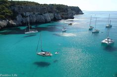 Boats look like they are not only floating on water, but in air Cala Macarella - Minorca Island, Spain