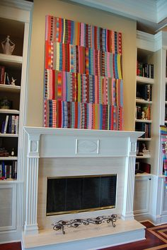 Simple and wonderful quilt art above the fireplace - love this splash of colour