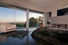 California-Modern-Luxury-Residence-with-white-black-bedroom-wall-big-window-sofa-pillow-bed-blanket-nightstand-lamp-and-carpet-and-hardwood-...
