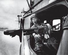 As Yankee Papa 13 approaches the landing zone, crew chief Farley opens fire with his M-60 machine gun at Vietcong positions. Larry Burrows took this picture with a camera mounted outside the copter on a special rig attached to the gun. As the gun swiveled, so did the rig, thus keeping the camera always pointed directly at Farley. Burrows triggered the camera by remote cable while squatting out of sight behind Farley.