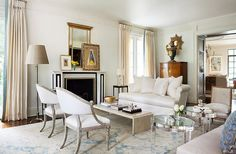 Inside Suzanne Kaslers Stunningly Serene Atlanta Home  -- Sophisticated living room in creams and neutrals with a touch of French blue, ornate carved chair legs, and modern acrylic side table. For more sophisticated traditional interior design ideas, see the full home tour on our Style Guide!