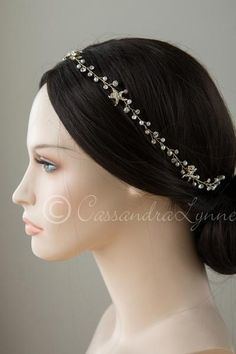 Five light gold, rhinestone dotted starfish accent a bridal hair vine of ivory…
