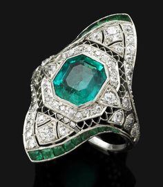 A Belle Epoque emerald and diamond ring, circa 1918  The central step-cut emerald surrounded by a border of old brilliant-cut diamonds, set within a finely pierced navette-shaped diamond-set plaque, to the calibré-cut emerald detail, to the shoulders of diamond-set bow motif, with pierced gallery and plain hoop, mounted in platinum, emerald weighing approximately 3.00 carats, diamonds approximately 1.15 carats total