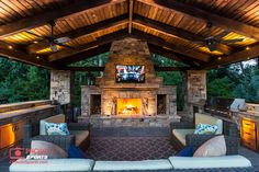 A pavilion with an outdoor kitchen, fireplace and an entertainment system.