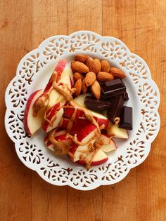 Sliced apples with raw almonds, dark chocolate, and drizzled peanut butter.